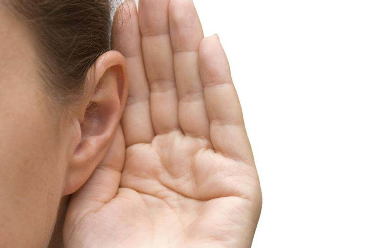 A woman trying to listen with her hand behind her ear.