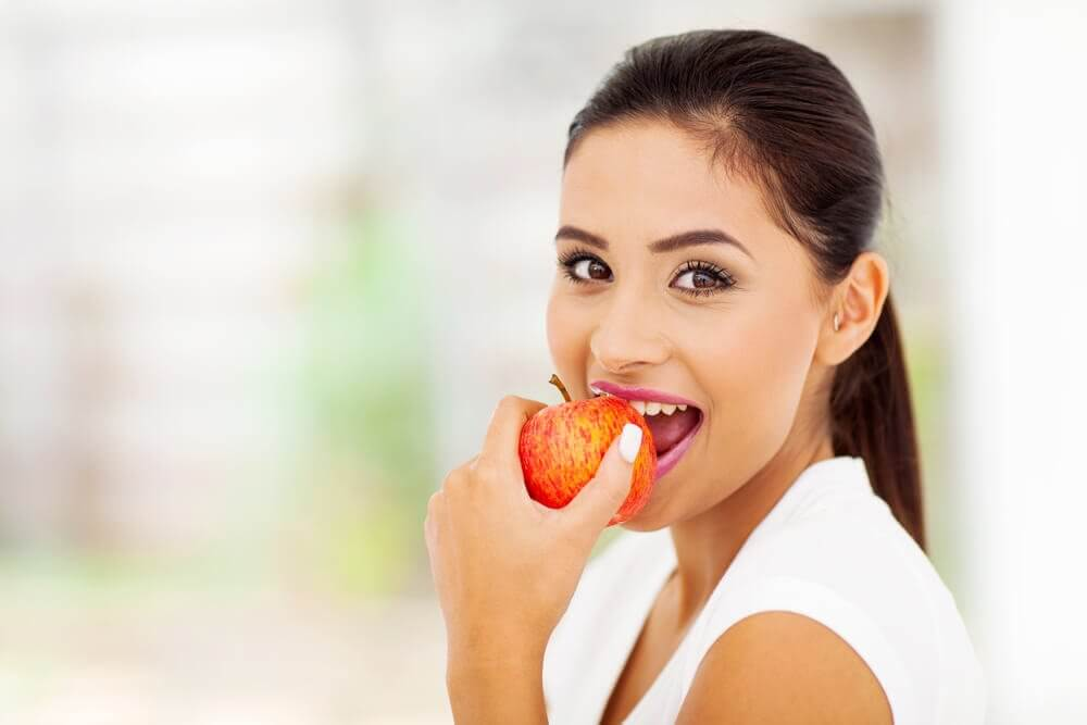 Woman eating an apple supplement to stop smoking