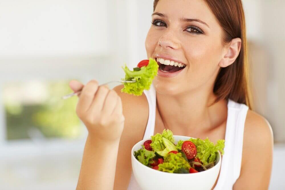 A happy woman eating a salad with tomatoes.