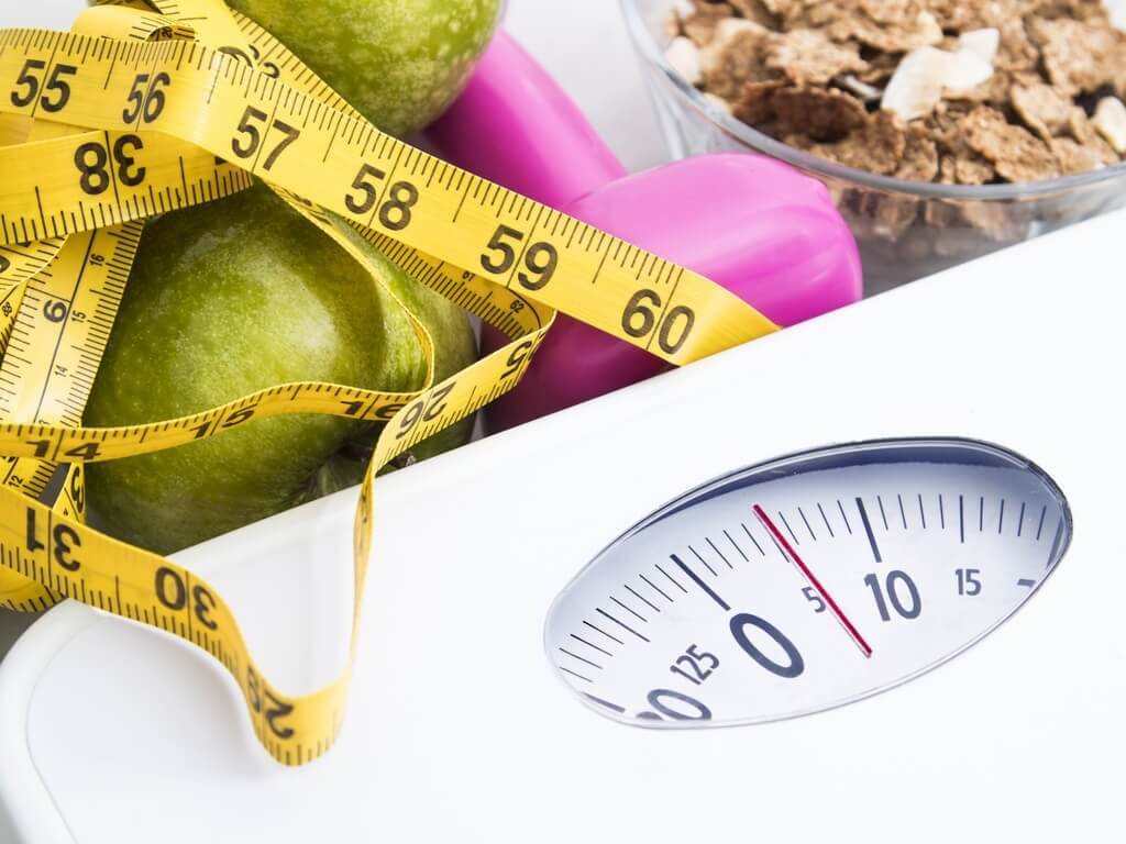 Losing weight: a tape measure and scale and fruit.