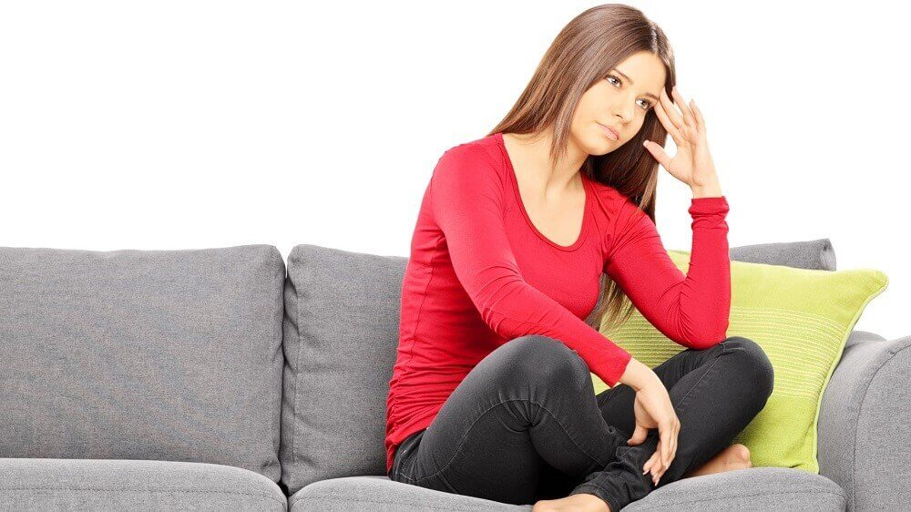 A woman sitting on a couch, upset.