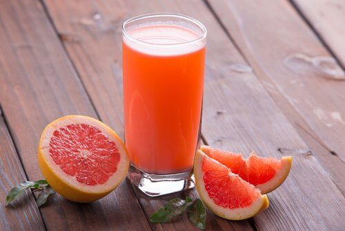 This is a glass of grapefruit juice beside sliced grapefruits.