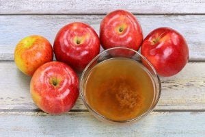 apple vinegar surrounded by apples