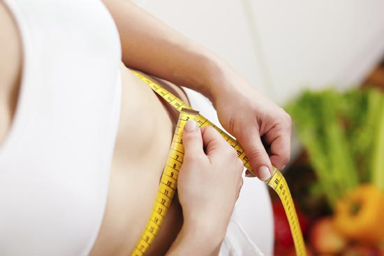 Weight gain and high cortisol: a woman measuring her waist