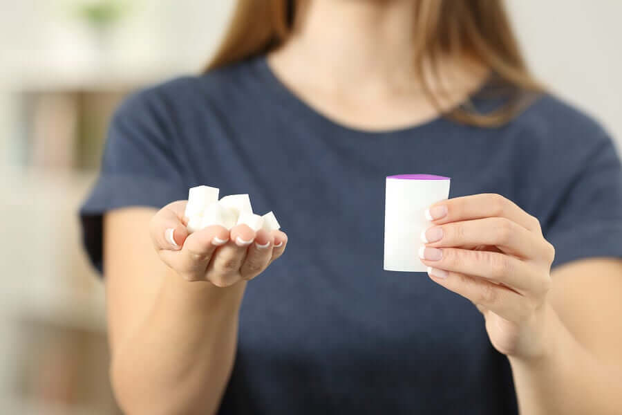 A woman holding sugar cubes and a packet of artificial sweetener in her hands.