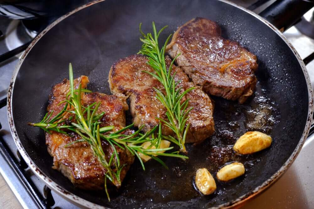 Beef, rosemary, and garlic cooked in a skillet.