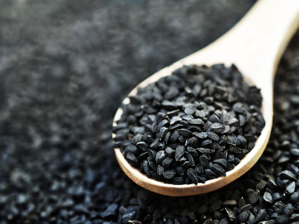black seed on a wooden spoon