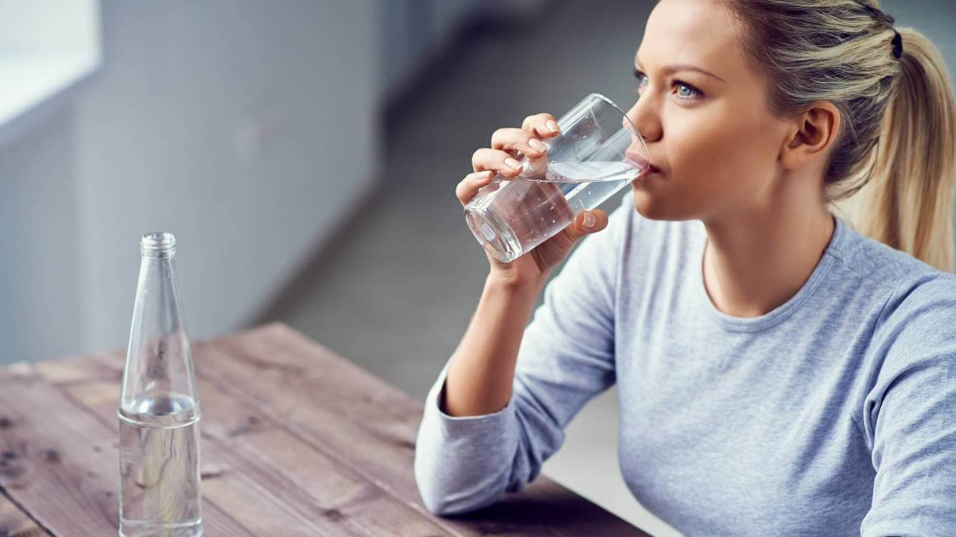 A girl drinking a glass of water.
