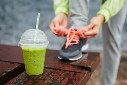 A runner getting ready for a run while drinking a green smoothie.
