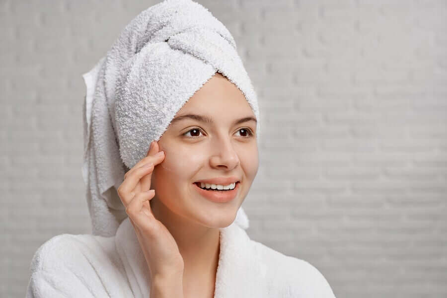 A woman with healthy skin smiling after getting out of the shower.