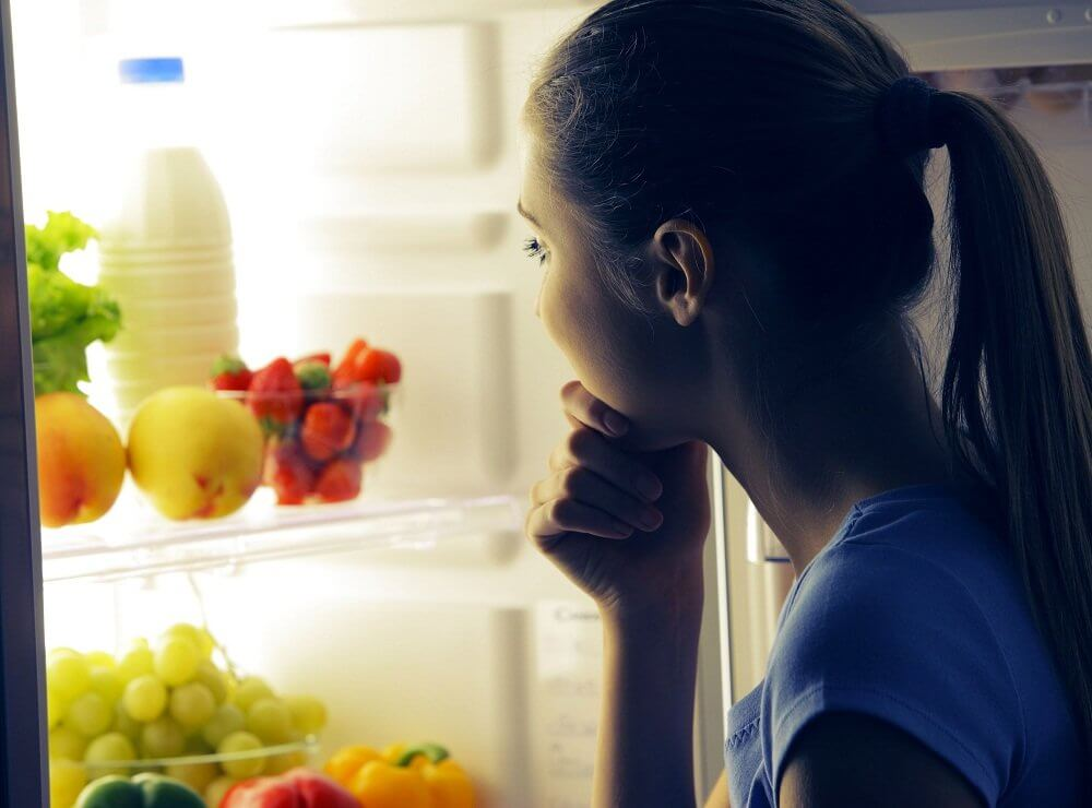 A woman looking at fruit and milk in the fridge at night.