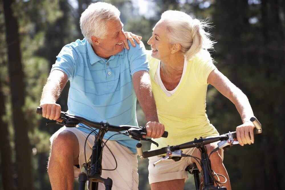 an elderly couple riding their bikes