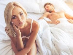 man asleep in bed and woman awake looking worried