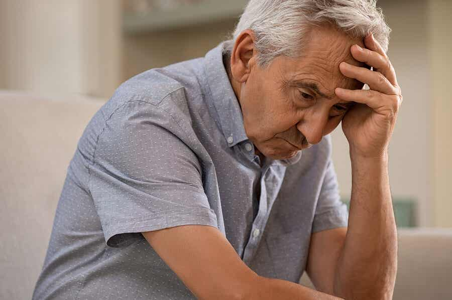 Alzheimer's disease: an older man holds his head with one hand.