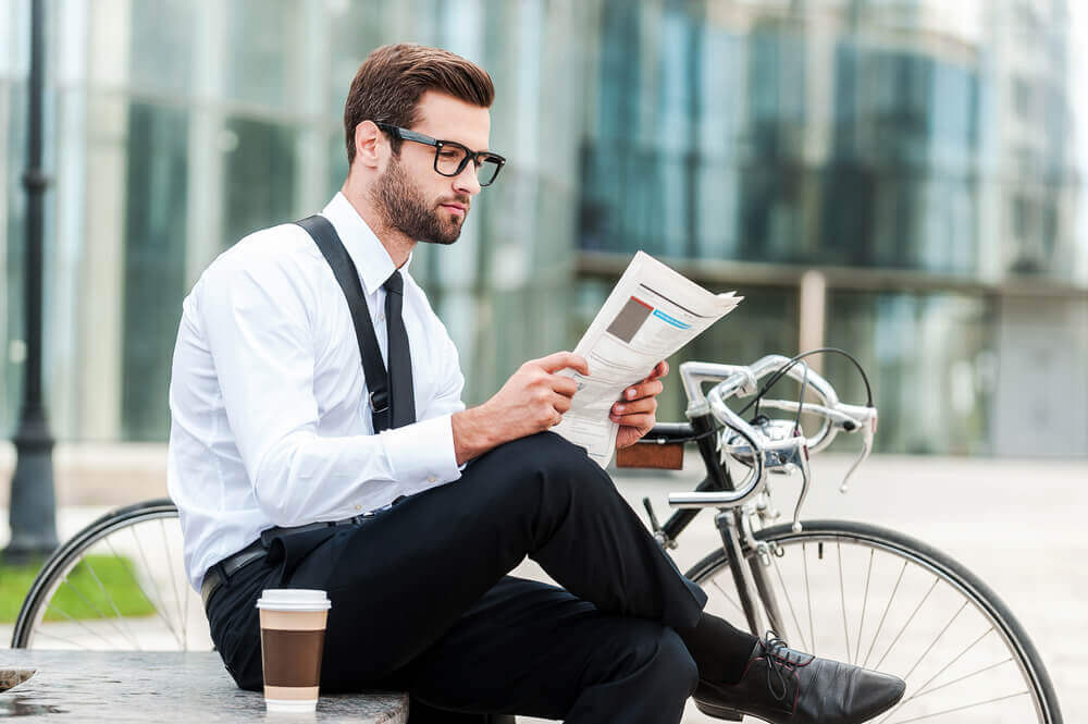 man with glasses reading a report