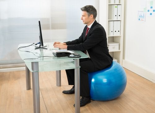 man sitting on exercise ball at an office