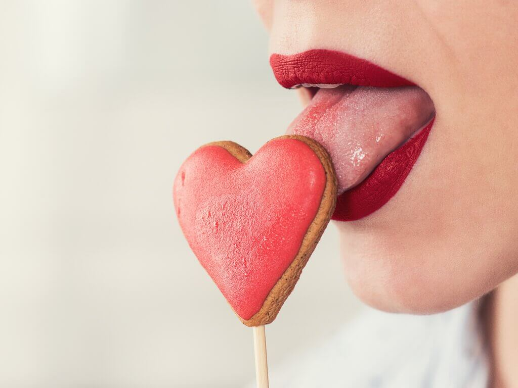 woman sucking on heart-shaped lollipop