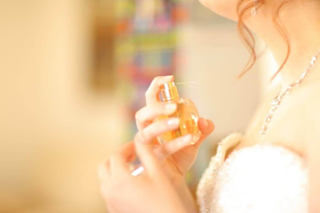 a woman putting on perfume