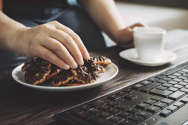 A person eating cookies in front of a computer.