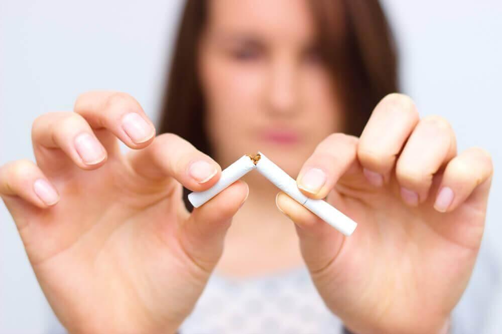 a woman breaking a cigarette in two