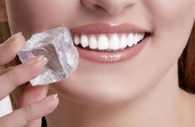 A woman applying ice to her mouth.