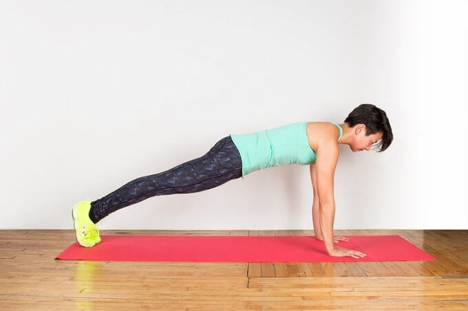 A woman doing a plank on top of mat.
