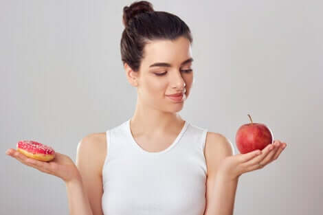 A woman deciding on an apple.