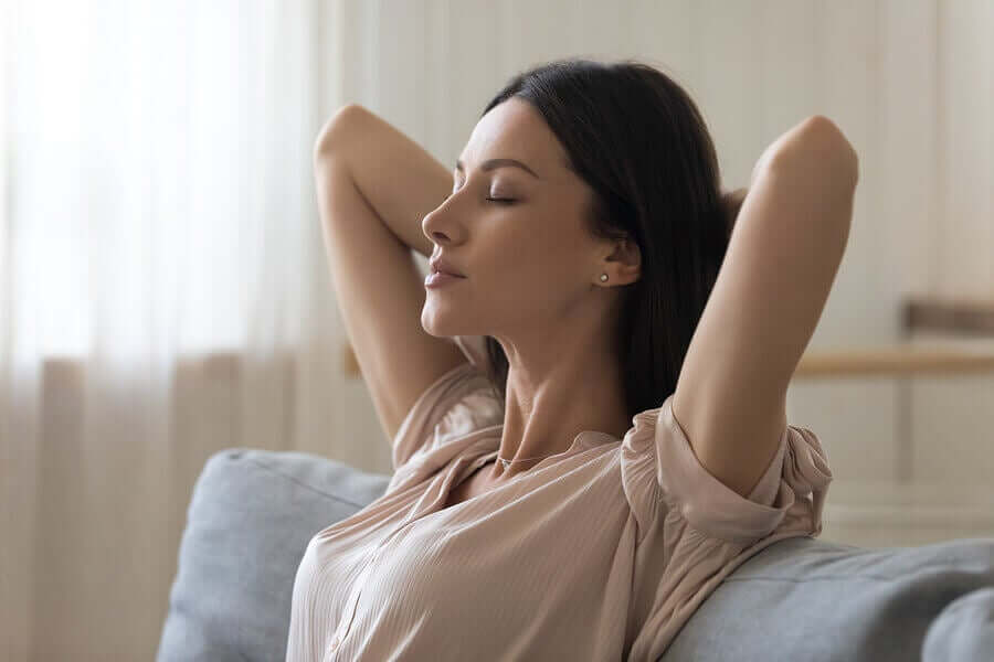 A woman doing deep breathing exercises with her eyes closed.