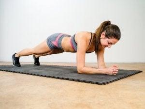 woman doing a plank on a yoga mat