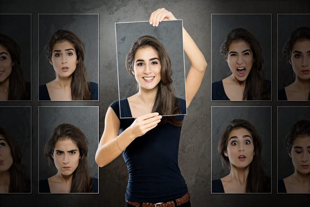 Woman with photos of many faces, each with a different emotion