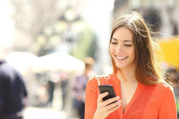 woman using her cell ohone and smiling