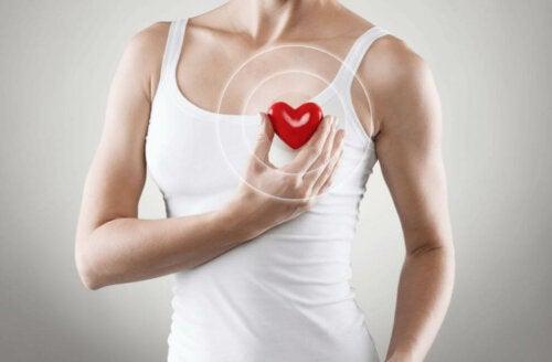 Kvinde holder plastikhjerte foran sit eget hjerte