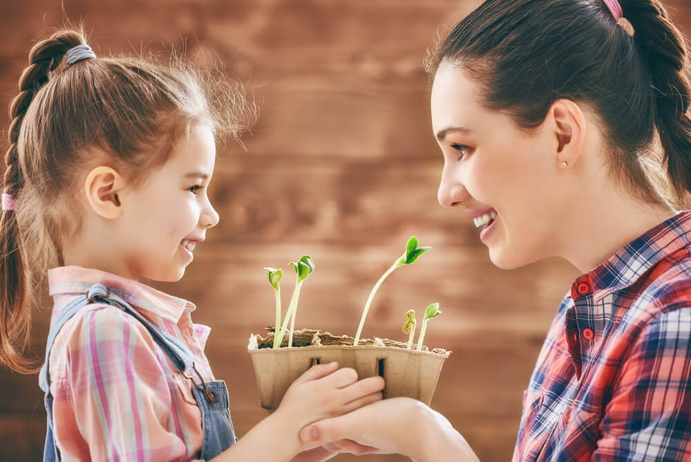 Mother planting flowers with daughter