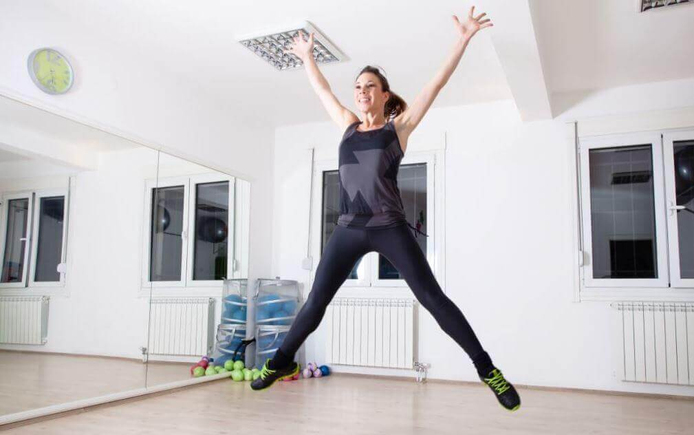 Woman doing jumping jacks.