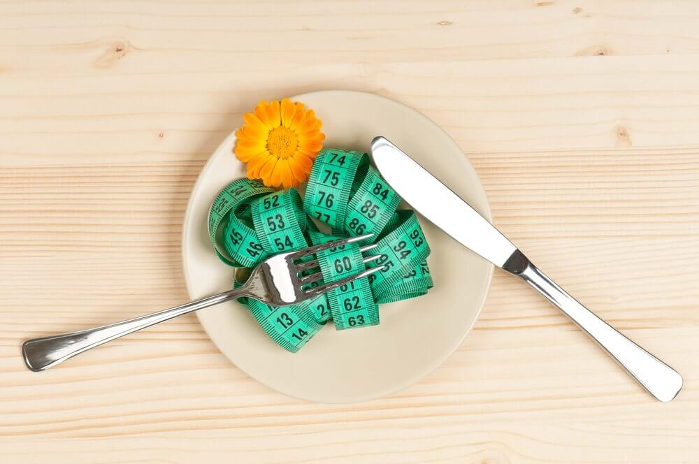 A measuring tape on a plate representing a diet.
