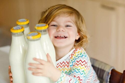 child hugging four bottles of milk smiling