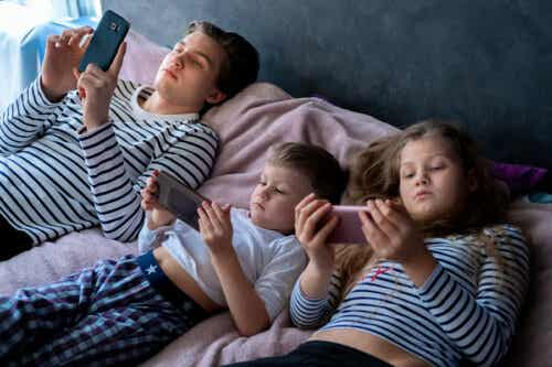 Children and teens using electronic devices in bed.