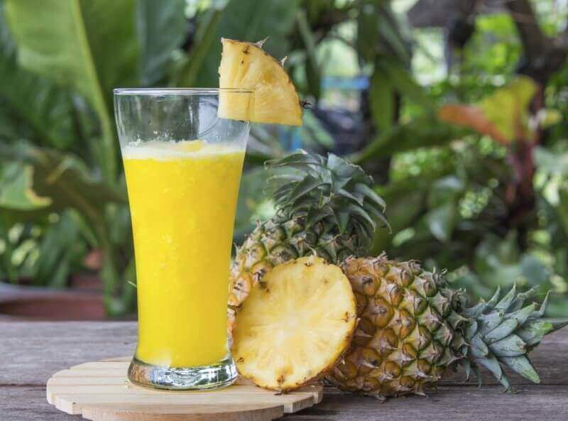 A pineapple smoothie next to a freshly cut pineapple.