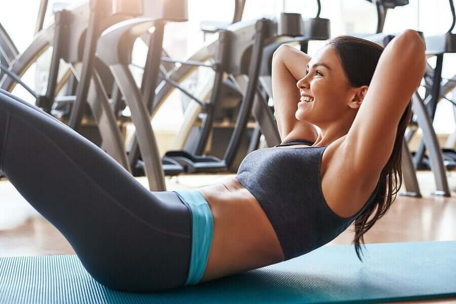 A woman doing situps at the gym.