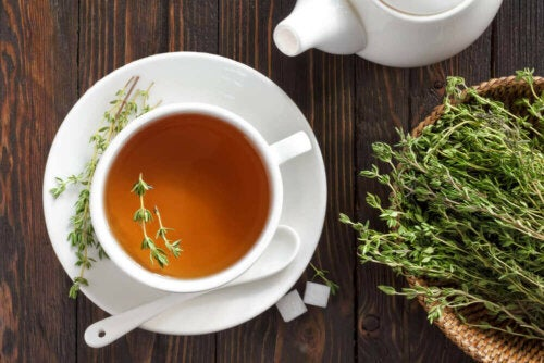 thyme tea in a china cup on a table with dried thyme for decoration