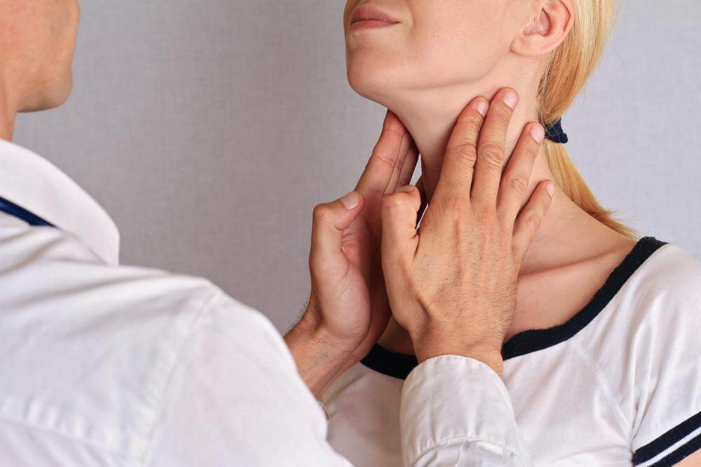 doctor checking woman's thyroid