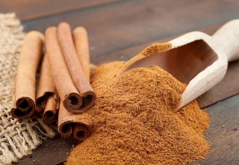 Cinnamon sticks next to some ground cinnamon