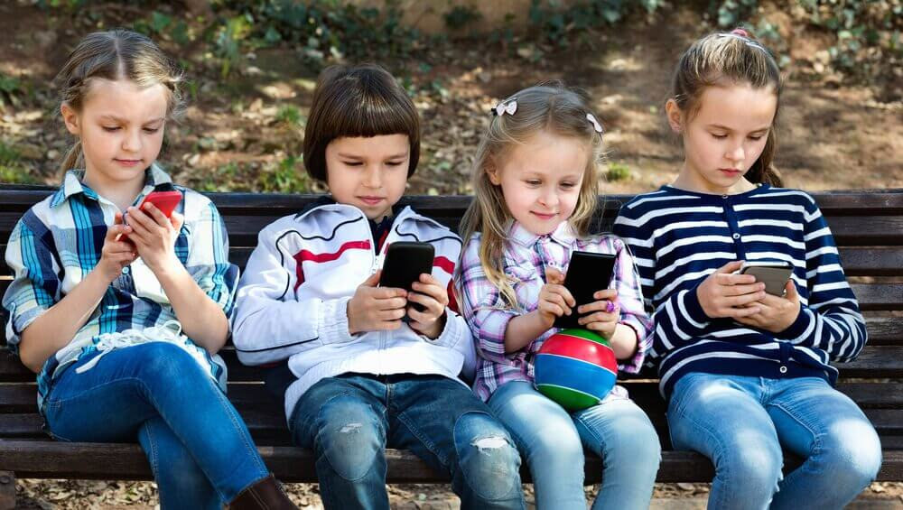 Four children on a bench on their phones