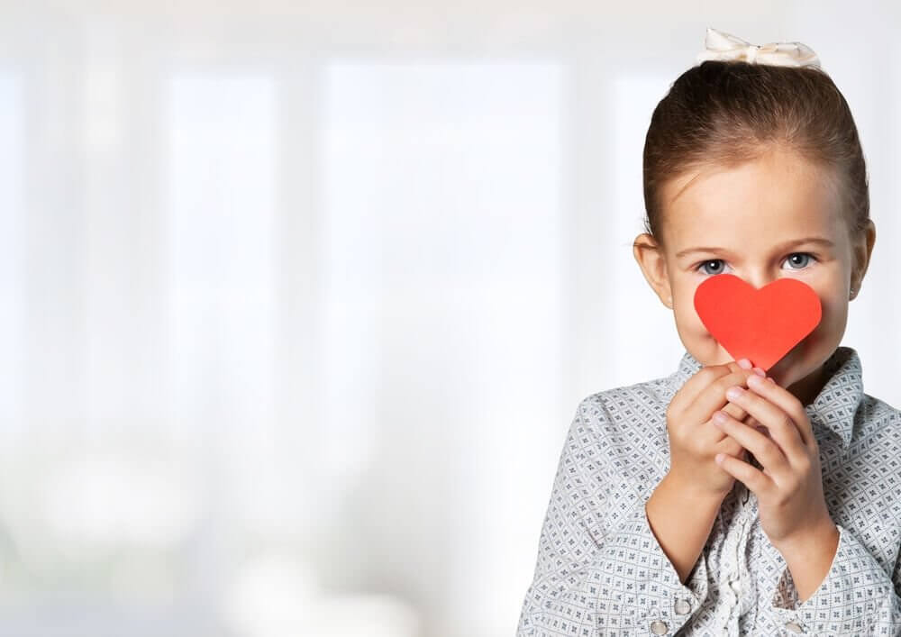 A potential crystal child holding a cardboard heart in front of her face