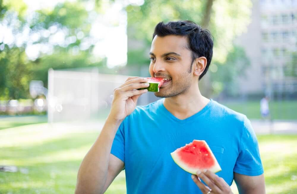 A man eating slices of watermelon