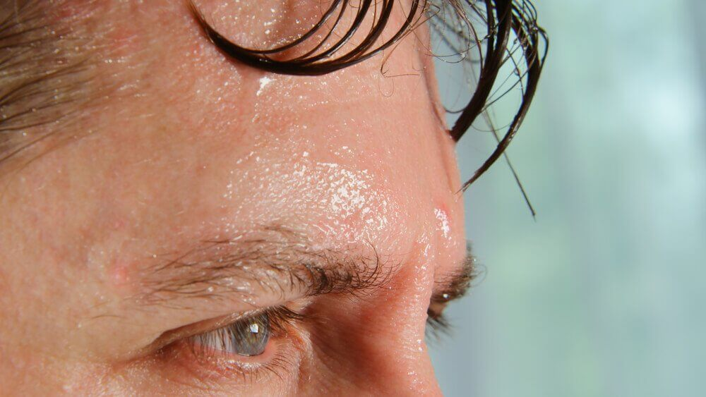 A man excessively sweating which is one of the symptoms of a cardiac arrest