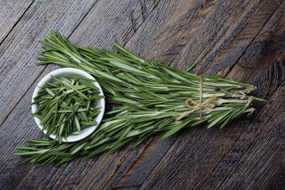 Rosemary and a bowl of rosemary leaves