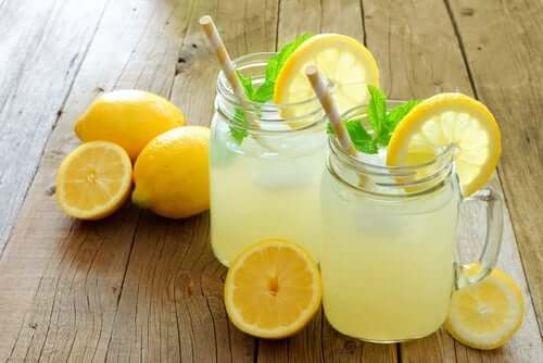 Some lemonade and lemons on a wooden table.