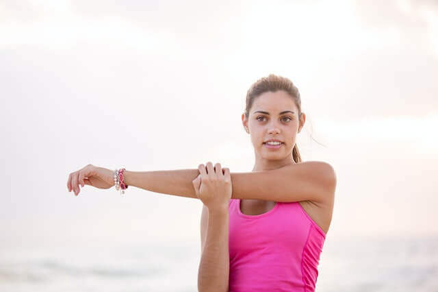 A woman stretching her arm.