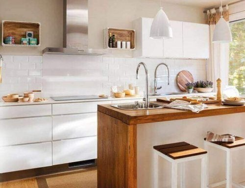 White colors and light colors neutral wood decorate a small kitchen
